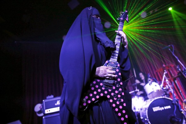 """Gisele Marie, a Muslim woman and professional heavy metal musician, plays her Gibson Flying V electric guitar during a concert in Sao Paulo December 16, 2014. Based in Sao Paulo, Marie, 42, is the granddaughter of German Catholics, and converted to Islam several months after her father passed away in 2009. Marie, who wears the Burka, has been fronting her brothers' heavy metal band """"Spectrus"""" since 2012. """"People do not expect to see a Muslim woman who uses a Burqa, practices the religion properly and is a professional guitarist who plays in a Heavy Metal band, so many people are shocked by it. But other people are curious and find it interesting, and others think that it is cool, but definitely, many people are shocked,"""" said Marie. Picture taken December 16, 2014. REUTERS/Nacho Doce       TPX IMAGES OF THE DAY"""