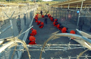 Detainees sit in a holding area watched by military police at Camp X-Ray inside Naval Base Guantanamo Bay, Cuba in this January 11, 2002 file photo during their processing into the temporary detention facility. The number of Guantanamo Bay prisoners taking part in a hunger strike that began nearly five months ago has surged to 84 since Christmas Day, the U.S. military said on December 29, 2005. EDITORIAL USE ONLY REUTERS/U.S. Department of Defense/Petty Officer 1st class Shane T. McCoy/Handout SECURITY GUANTANAMO HUNGER 2006-5038.JPG